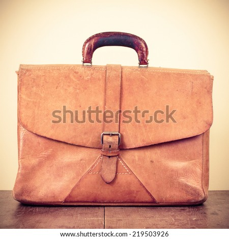 Old retro leather school bag on wooden desk - stock photo