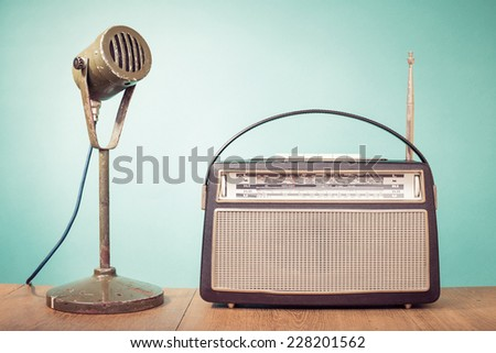 Old retro microphone and portable radio on table front mint green background  - stock photo