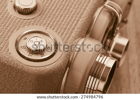Old retro 8 mm movie camera lying on wooden table. Film nostalgia containing old-fashioned home movie equipment.  - stock photo