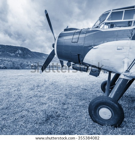 Old retro plane on the meadow by the mountains. - stock photo