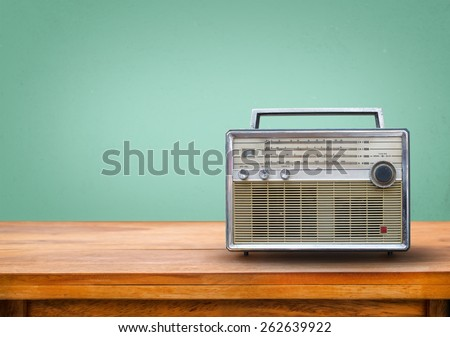 Old retro radio on table with vintage green eye light background - stock photo