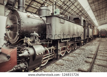 Old retro steam train locomotive in station - stock photo