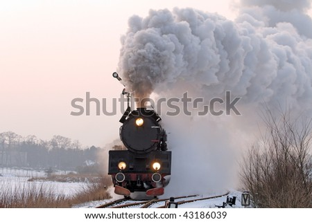 Old retro steam train starting from the station during wintertime - stock photo