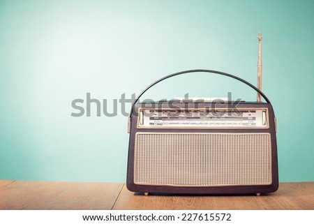 Old retro style portable radio front mint green background  - stock photo