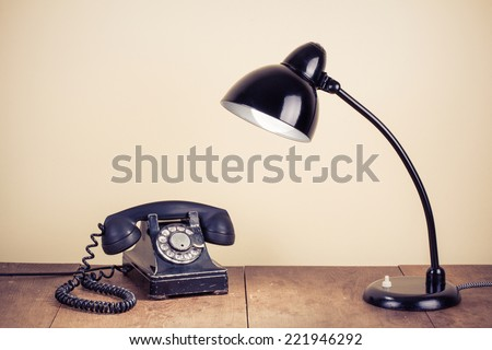 Old retro telephone and desk lamp on wooden table - stock photo