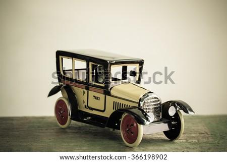 Old retro toy yellow taxi. - stock photo