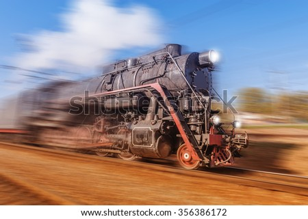 Old retro train with steam locomotive moves fast. - stock photo