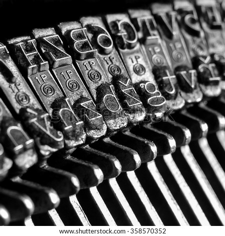 old retro type-setting machine closeup on letter; detail