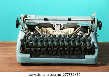 Old retro typewriter on table on green background - stock photo