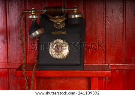 Old retro vintage rotary dial-up telephone instrument with a handset and cradle mounted on a red wooden wall - stock photo