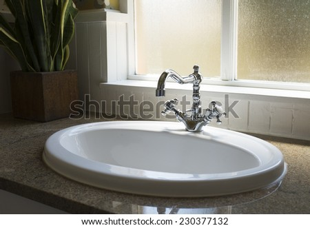 Old retro water tap basin in modern bathroom toilet with window - stock photo