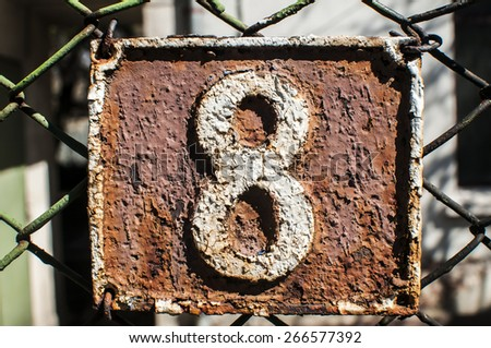 Old retro weathered painted cast iron plate with number 8 - stock photo