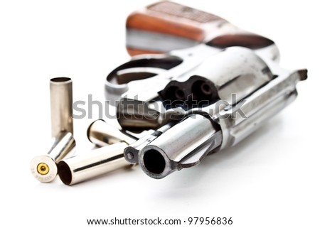 old .38 revolver handgun with used bullet shells on white background