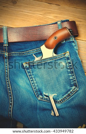 old revolver in the pocket with a hole in old blue jeans with a leather belt. instagram image filter retro style - stock photo