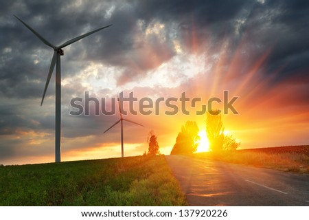 Old road and wind power generators against a dramatic sunset - stock photo