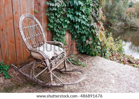 old rocking chair on the front porch of an  house. wooden wall with vine grapes