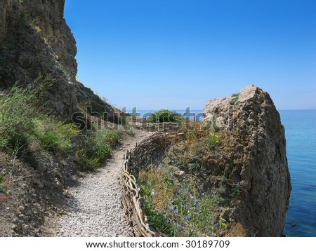 Old rocky footpath above the sea - stock photo
