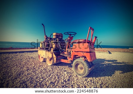 Old Roller (paver) prepare the ground for the laying of asphalt. Vintage style - stock photo