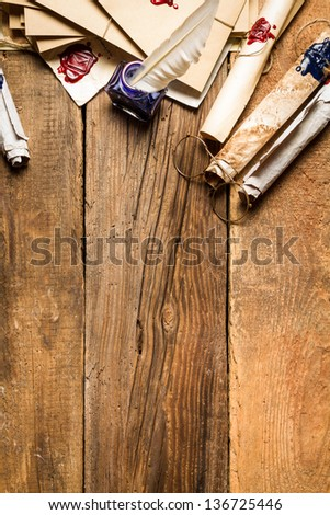 Old rolls of paper, glasses and blue ink in the inkwell as vintage background - stock photo