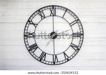 Old roman numeral clock on a wooden background - stock photo