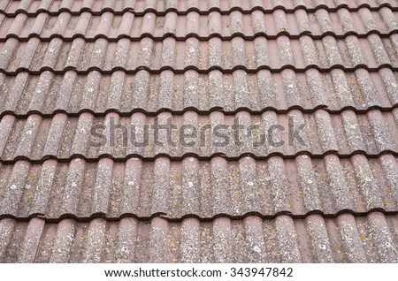 Old roof with ceramic tiles closeup in cloudy day