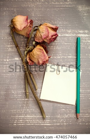 Old roses and blank sticky note with pencil.