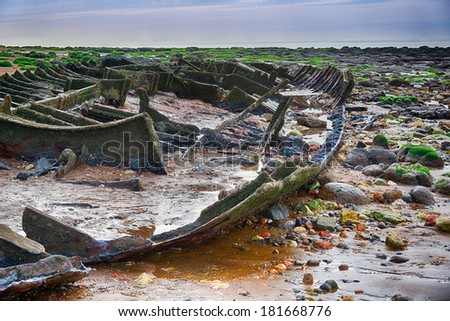 Old rotting concrete boat on the seashore - stock photo
