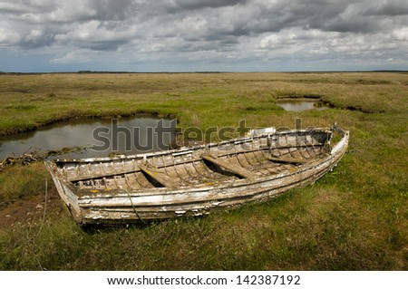 Old rotting wooden rowing boat at Brancaster Norfolk England - stock photo