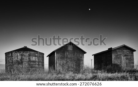 Old round grain bin and two square weathered storage sheds beneath the moon in black and white
