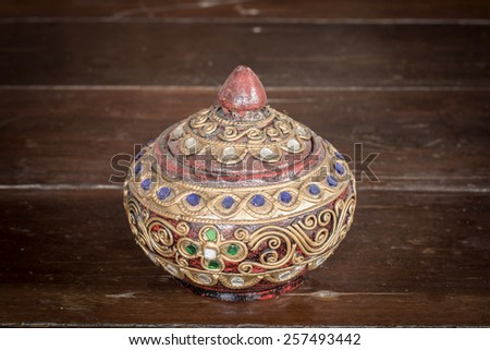 old round wood casket on wooden board background - stock photo