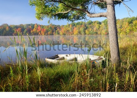 Old rowboat on the shore of a small Michigan lake in autumn. - stock photo