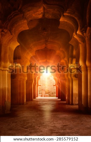 Old ruined arch in ancient palace at sunset, India - stock photo