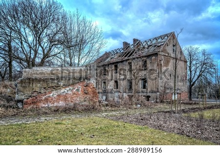 Old ruined building. Left collapsing house, the object falling into ruin is probably inhabited by homeless people. - stock photo
