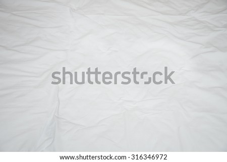 Old rumpled bed sheet with creases. View from above - stock photo