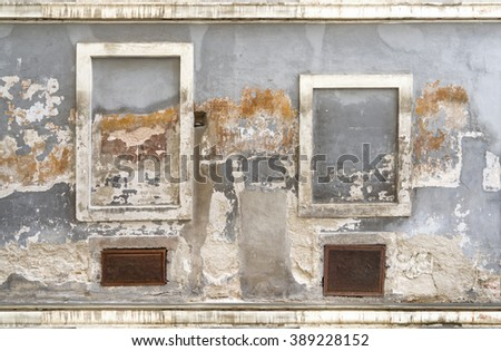 Old rundown facade of the ruin of a house with two differently sized, walled up windows and two basement grids  - stock photo