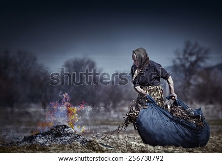 Old rural woman burning fallen leaves, spring cleaning in the garden - stock photo