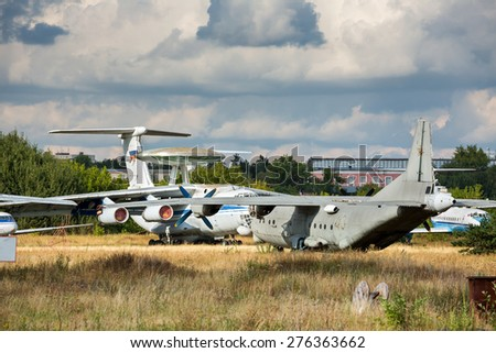 Old russian aircrafts at the abandoned aerodrome in summertime. Cemetery of large and small aircraft near the runway - stock photo