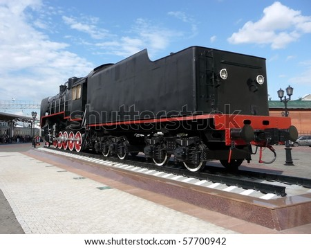 Old Russian black locomotive on a background of blue sky