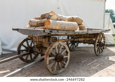 Old Russian wooden cart, wagon with firewood on one show ethnocultures Russia. Truck loaded with wood and stands without a horse - stock photo