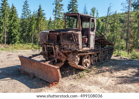 old rust vintage caterpillar tractor standing near the forest