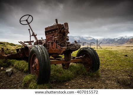 Old rusted abandoned tractor on a farm  - stock photo