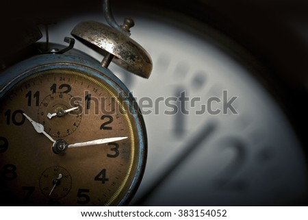 Old rusted alarm clock with another larger clock face in the background - stock photo