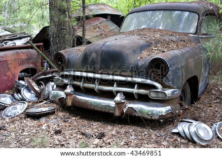 Old rusted car in junk yard - stock photo