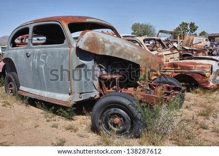 old rusted car without an engine in a junkyard - stock photo