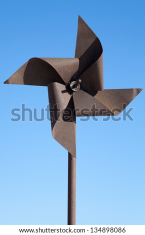 Old rusted metal wind whirligig above blue sky - stock photo