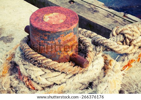 Old rusted mooring bollard with naval ropes on concrete pier, vintage toned photo with old style instagram filter effect - stock photo