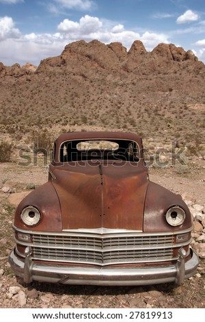 Old Rusted Out Car in the Desert Landscape - stock photo