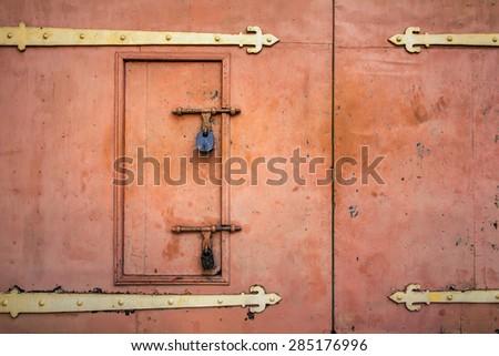 Old rusted padlock hanging on gray metal retro door - stock photo
