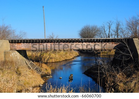 Old rusted train bridge with blue sky and creek - stock photo