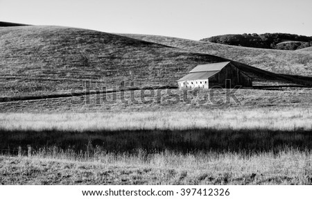 Old rustic barn located in meadow lands in the hills of California - stock photo